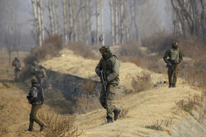 Indian police and Paramilitary Central Reserve Police Force (CRPF) men patrol near a building which was held by militants in Lathipora Pulwama, south of Srinagar, the summer capital of Indian Kashmir, on Dec 31, 2017.