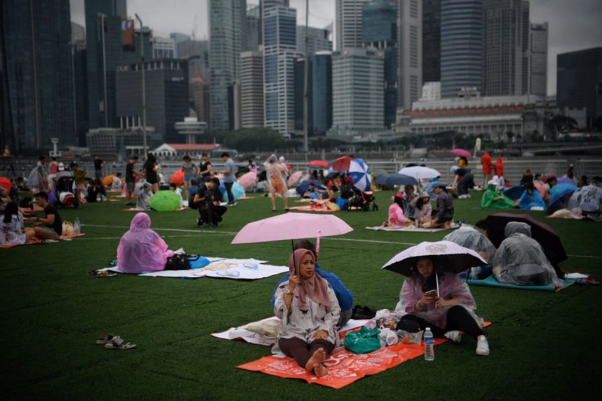 People shielding themselves from the rain while waiting for the fireworks at the Marina Bay Floating Platform at 6pm on Dec 31.