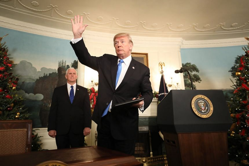 US President Donald Trump waves after signing an order recognising Jerusalem as the capital of Israel on Dec 6, 2017.