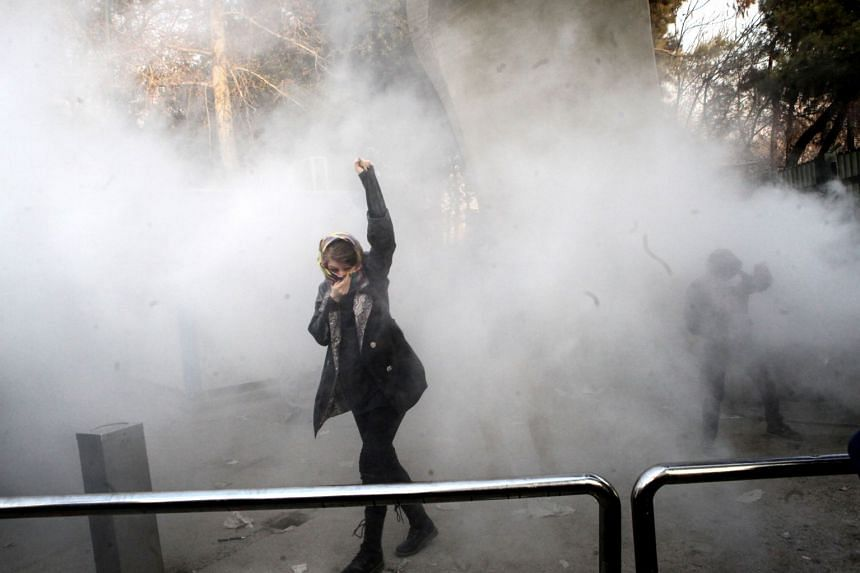 Iranian students clash with riot police during an anti-government protest around the University of Teheran.
