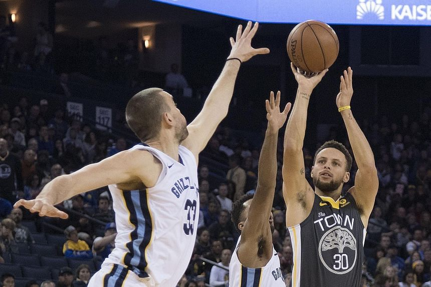 Golden State Warriors guard Stephen Curry shoots while guarded by Memphis Grizzlies centre Marc Gasol (left) and guard Andrew Harrison. The Warriors won 141-128 on Saturday.