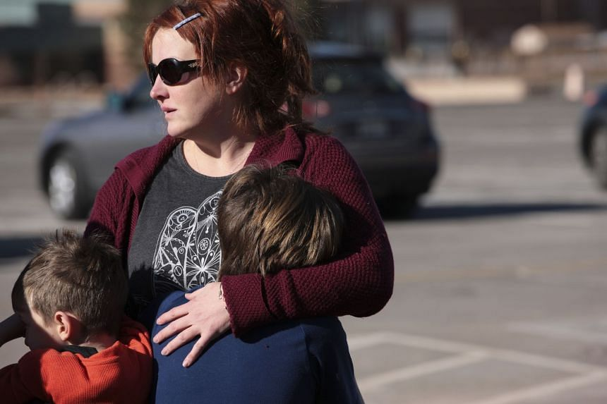 Courtney Branscome embraces her sons Mason Glauser, 10, and Sawyer, seven, after placing flowers at a makeshift memorial.