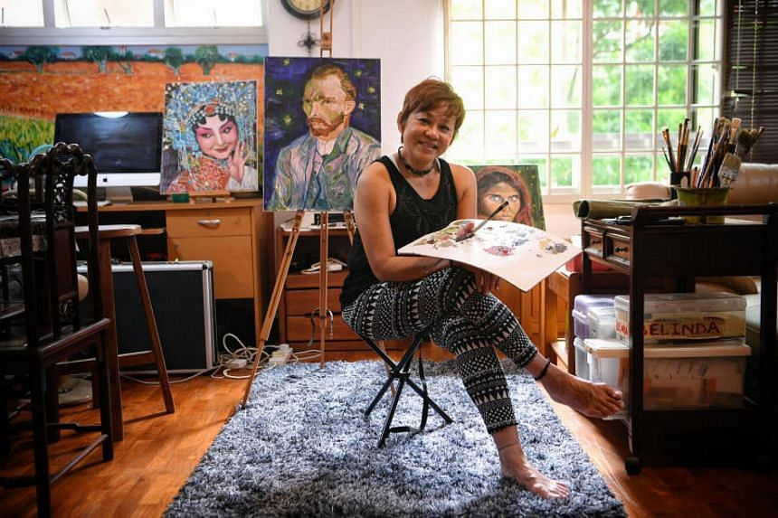 Ms Belinda Low pictured at home with some of her paintings.