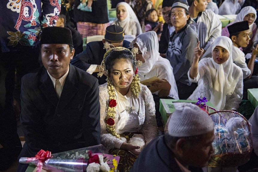 A couple looks on as they attend a mass wedding to welcome and celebrate the New Year 2018 in Jakarta.