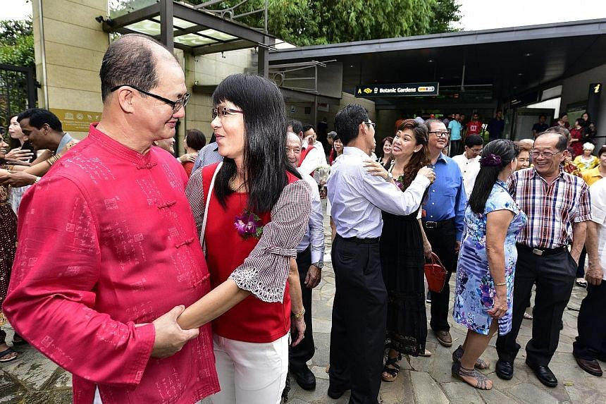 Operation Coordinator Teoh Chin Chong (left), 52 , and his wife, housewife Winnie Sia Kie Hee, 51, were among the 32 couples who reaffirmed their marriage vows outside Botanic Gardens MRT station, as part of a grassroots initiative to promote family
