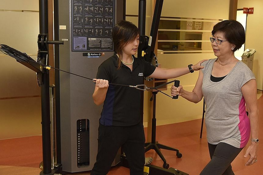 Exercise physiologist Shayne Hu guiding Ms Tay Cheng Choo at a cable machine. Ms Tay had a large chunk of her thigh muscle removed in an operation, but has regained much strength and is even dancing again.