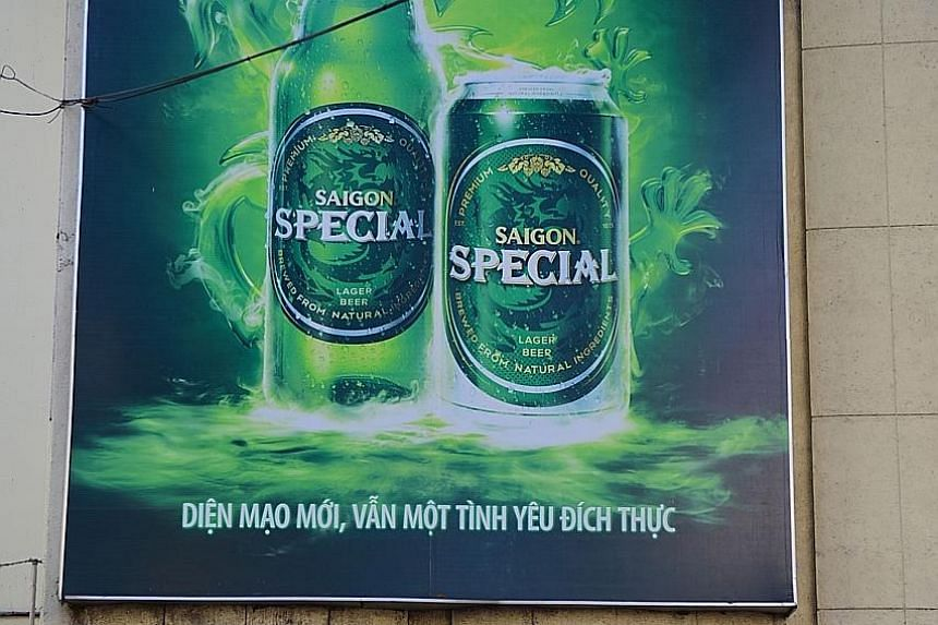People ride past beer advertising outside Sabeco's main brewery in Ho Chi Minh City. Thai Bev acquired a 53.6 per cent stake in Vietnam's largest state-owned brewer last month.