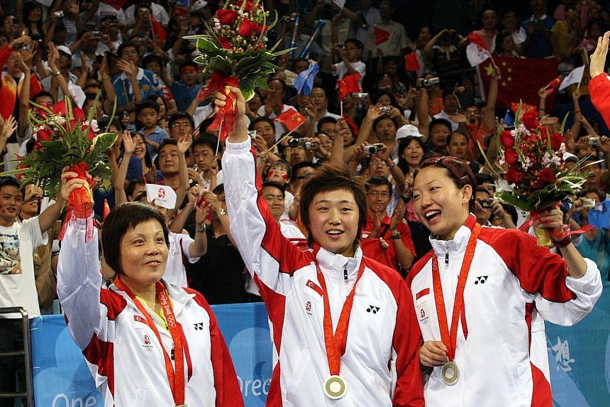 From left: Singapore's Wang Yuegu, Feng Tianwei and Li Jiawei celebrating after winning silver in the team event at the 2008 Beijing Olympics.