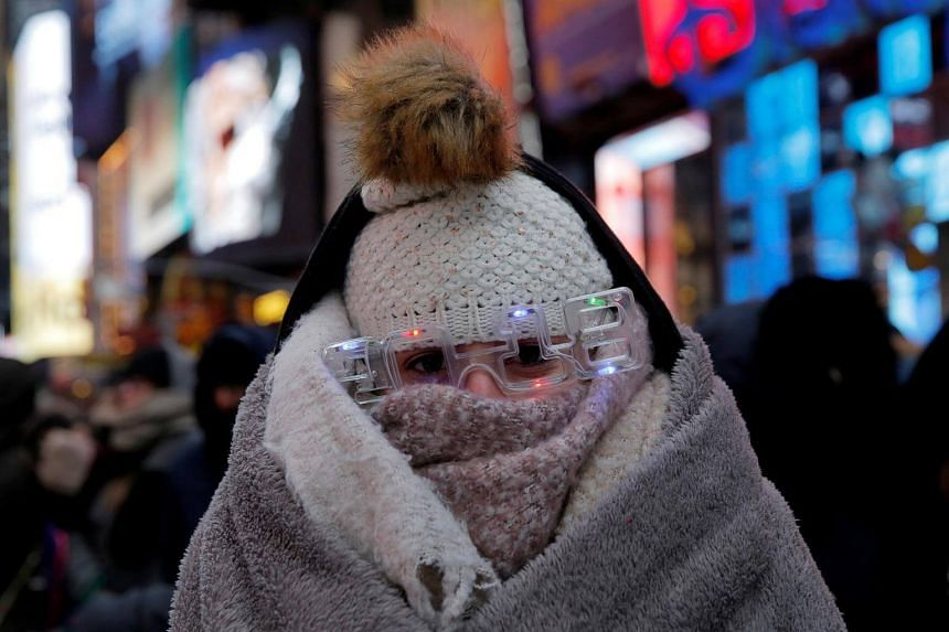 A reveller waits in Times Square during a cold weather front ahead of New Year's celebrations in Manhattan, New York.