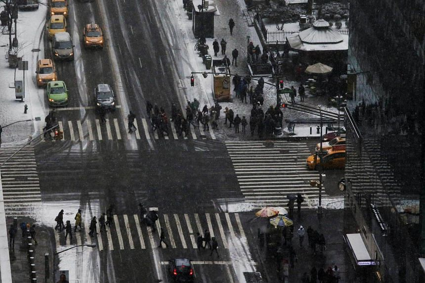 People cross 6th Avenue and 42nd Street as a cold weather front hits the region, in Manhattan, on Dec 30, 2017.