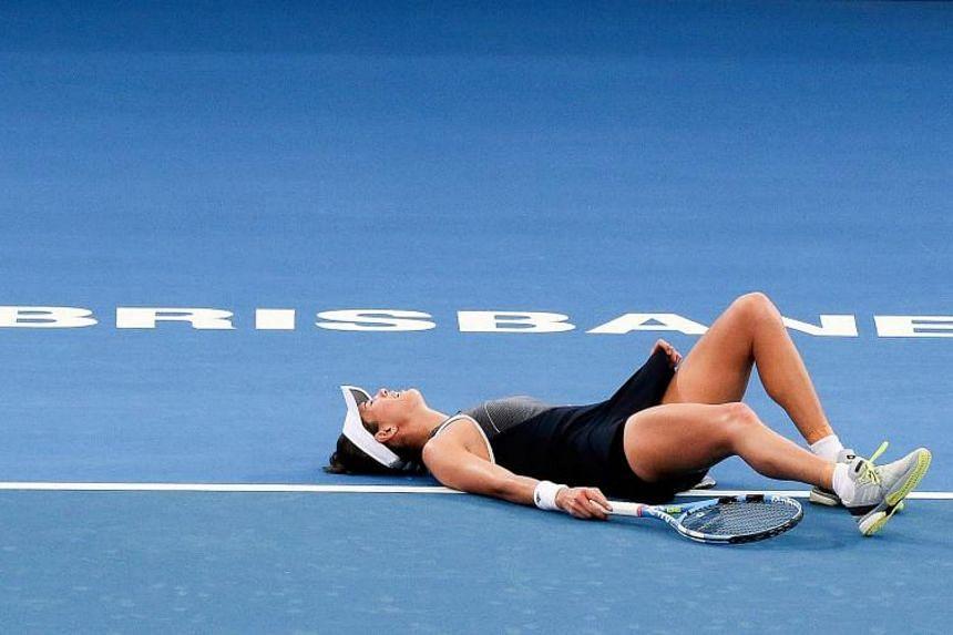 Garbine Muguruza reacts before retiring from her second round match against Aleksandra Krunic at the Brisbane International tennis tournament.