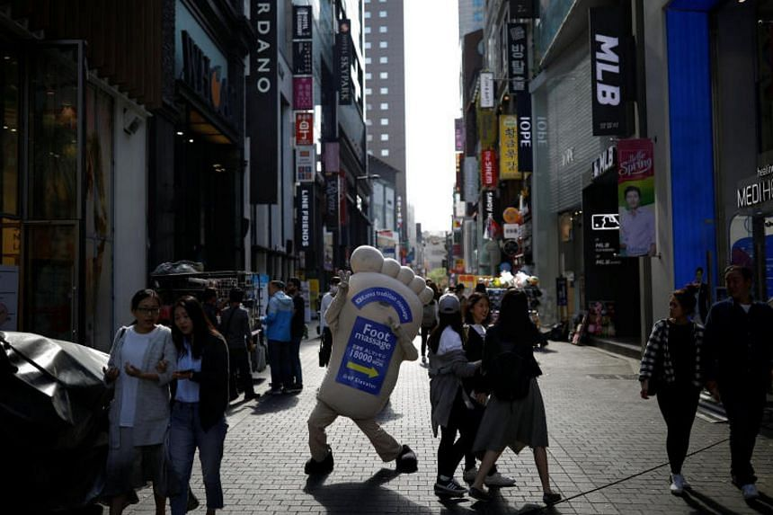 A promoter of a foot massage shop in Seoul's Myeongdong shopping district on April 26, 2017.