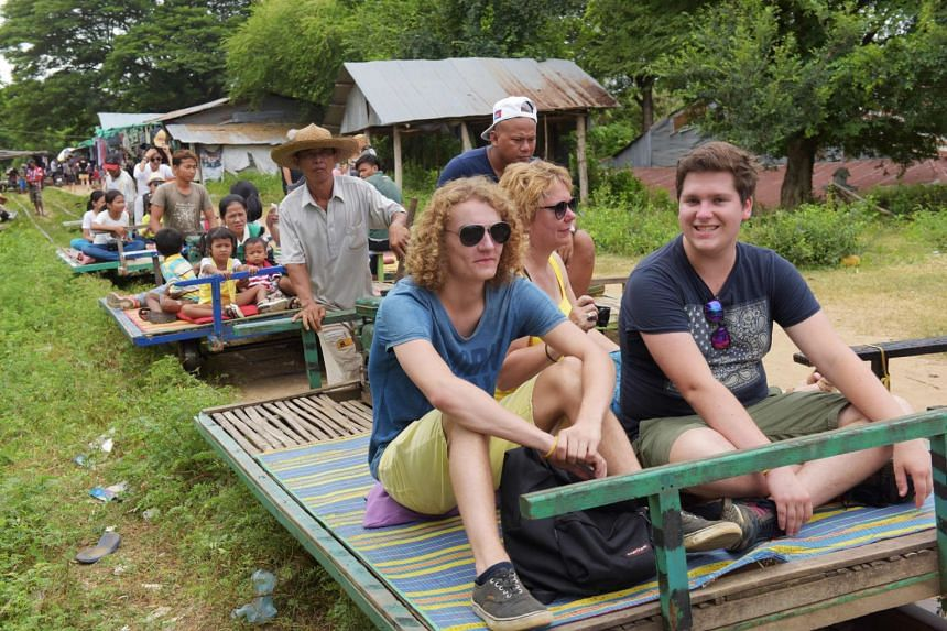 Tourists ride bamboo-lined flat trollies on one of Cambodia's abandoned colonial-era train tracks in Battambang.