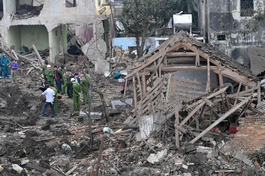 Soldiers and rescuers stand at the site of a big explosion that razed five homes and shattered windows of surrounding buildings in the northern province of Bac Ninh on Jan 3, 2018.