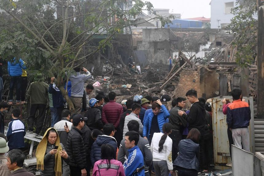 Villagers look at the site where a big explosion razed five homes and shattered windows of surrounding buildings in Bac Ninh, Vietnam, on Jan 3, 2018. PHOTO: AFP