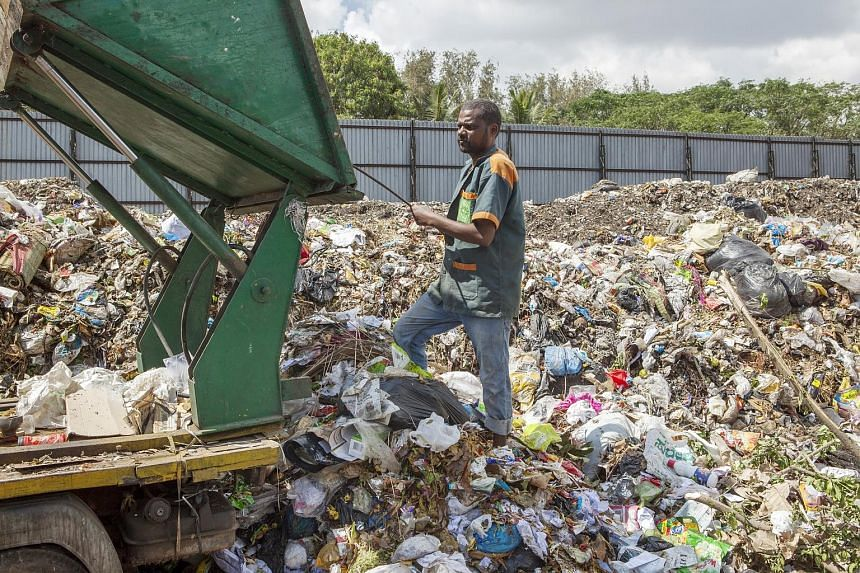 A worker removing non-segregated waste from a cargo vehicle at a compost plant in Mysuru, India. The trash is sorted, with reusable items sold to scrap dealers and the remainder composted and sold to farmers.