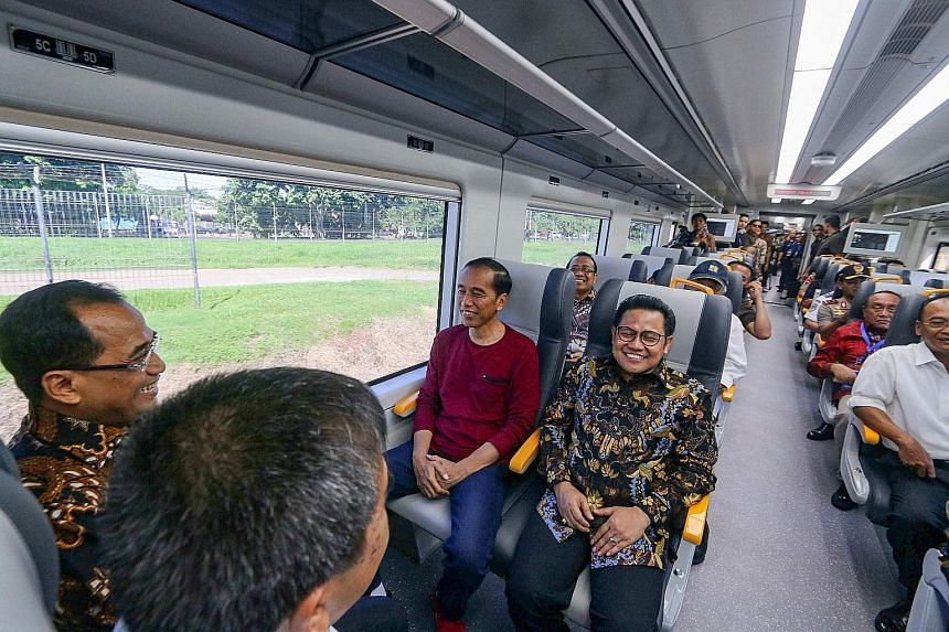 Indonesian President Joko Widodo (in purple T-shirt) taking a ride on the newly launched airport train linking Soekarno-Hatta International Airport to the Jakarta city centre yesterday. The train connection comes as the sprawling Indonesian capital m