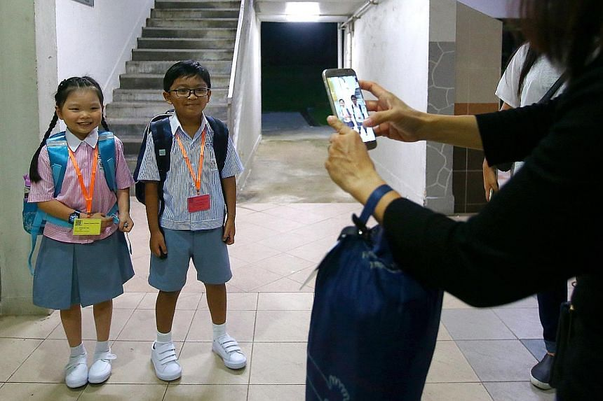 From left: Muhammad Aiman Aqmal Nor Md having breakfast before his first day at Shuqun Primary School, and then stopping for a photo with his neighbour Grace Tng. Right: Grace, too, is all set to head to school for her first day. Form teacher Lily Ye