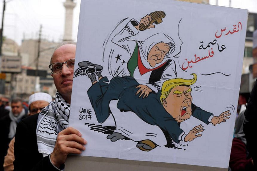 "A man holds a placard reading ""Jerusalem is the capital of Palestine"" during a protest against US President Donald Trump's recognition of Jerusalem as Israel's capital, in Amman, Jordan on Dec 29, 2017."