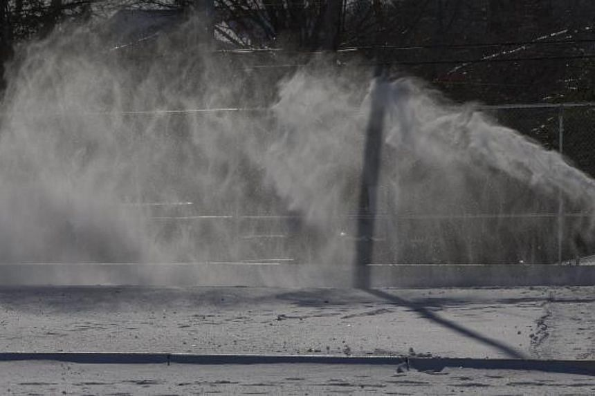 A town recreational employee clears snow from an outdoor skating rink in Burlington, Massachusetts on Jan 2, 2018.