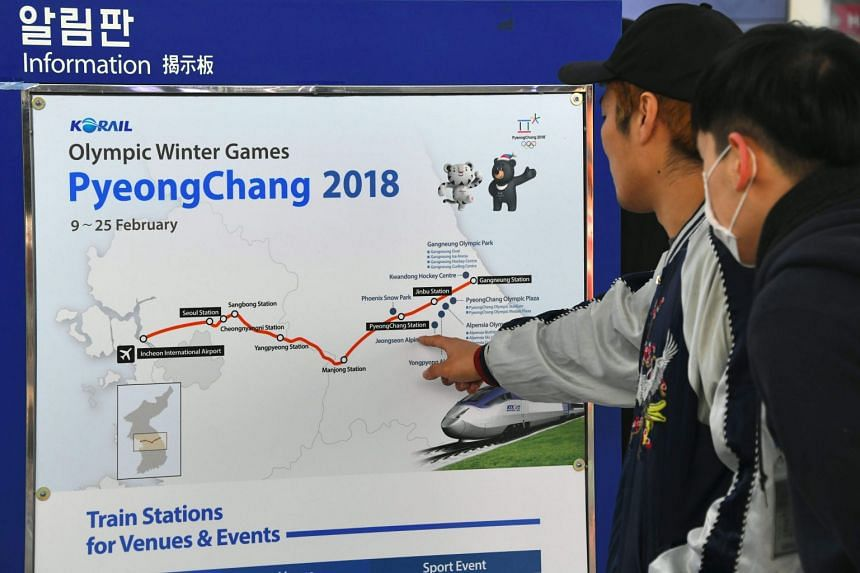 Travellers looking at an information board for a new high-speed train line for the 2018 PyeongChang Winter Olympic Games, at Seoul station on Dec 22, 2017.