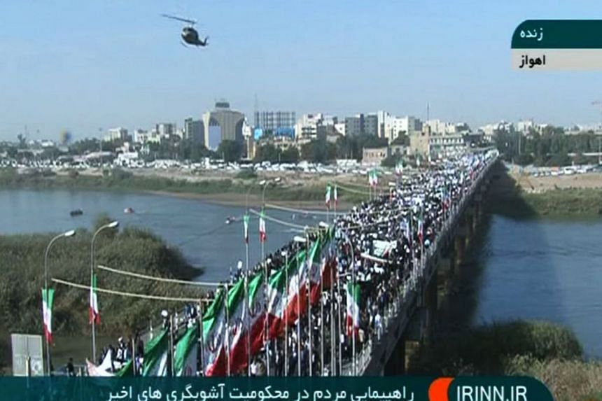 Pro-government demonstrators march through the streets of the southwestern Iranian city of Ahvaz.