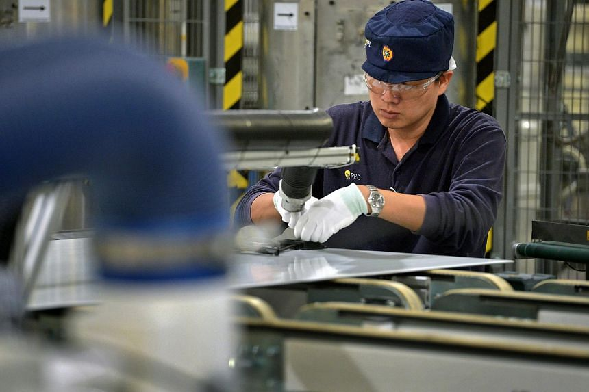 An employee works on solar panels on the module production line at the REC Solar ASA manufacturing facility at Tuas.