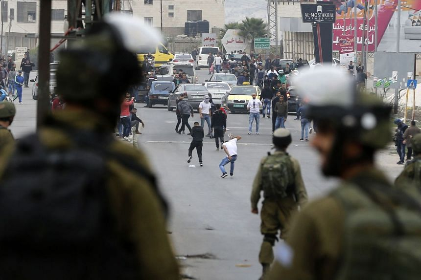 Israeli security forces are seen facing Palestinian protesters near the Huwara checkpoint, south of Nablus in the Israeli-occupied West Bank, on Dec 22, 2017.