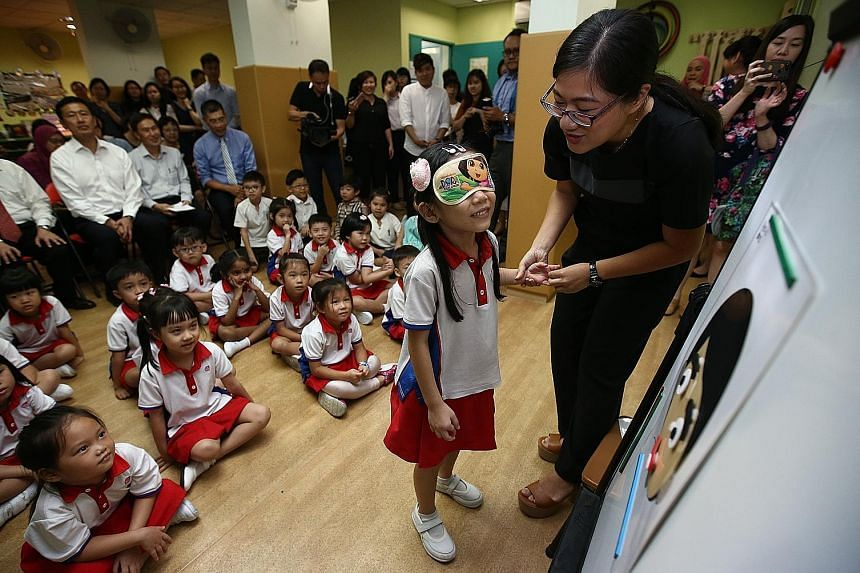 Children at PCF Sparkletots pre-school in Gambas attending a Chinese lesson yesterday using materials designed by the Confucius Institute. Looking on are (seated, from far left) Minister Ong Ye Kung, CI-NTU director Neo Peng Fu and Mr Victor Bay, chi