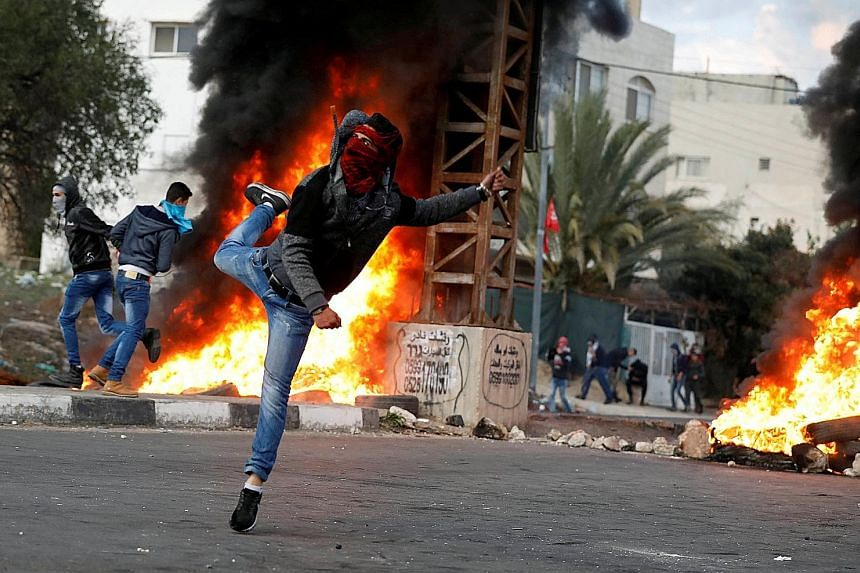 A Palestinian demonstrator hurling stones at Israeli troops during clashes at a protest near the West Bank city of Nablus last Friday against US President Donald Trump's decision to recognise Jerusalem as the capital of Israel.
