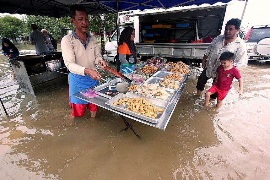 A food seller in Sungai Isap Damai Park in Kuantan continuing to work yesterday despite the flooding. The floods had forced 11 schools in Pahang to remain closed on Tuesday on the first day of the new school year.