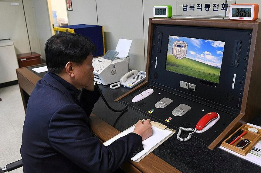 A South Korean official checking the direct communications hotline with the North Korean side at the border village of Panmunjom in South Korea yesterday. Pyongyang had suspended the hotline in February 2016 in protest against Seoul closing down the