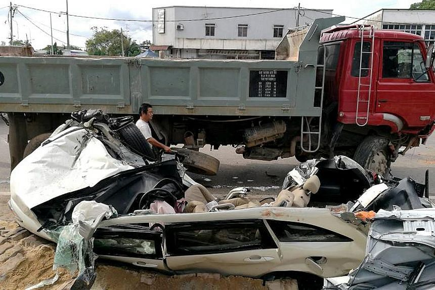 The white Honda Stream was crushed by the tipper truck, which had to be lifted using a crane to free the car.
