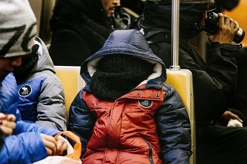 A commuter in New York all bundled up for the cold. The eastern US, now in the grip of a cold snap, will see freezing rain, snow and strong winds.