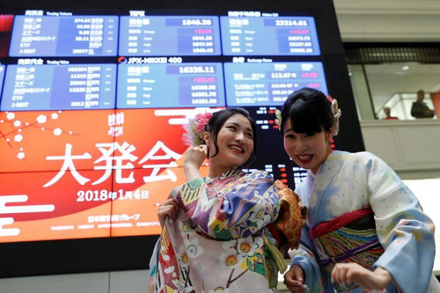 Women, dressed in ceremonial kimonos, smile in front of an electronic board displaying the Nikkei average on the first day of trading in 2018 at the Tokyo Stock Exchange  on Jan 4.