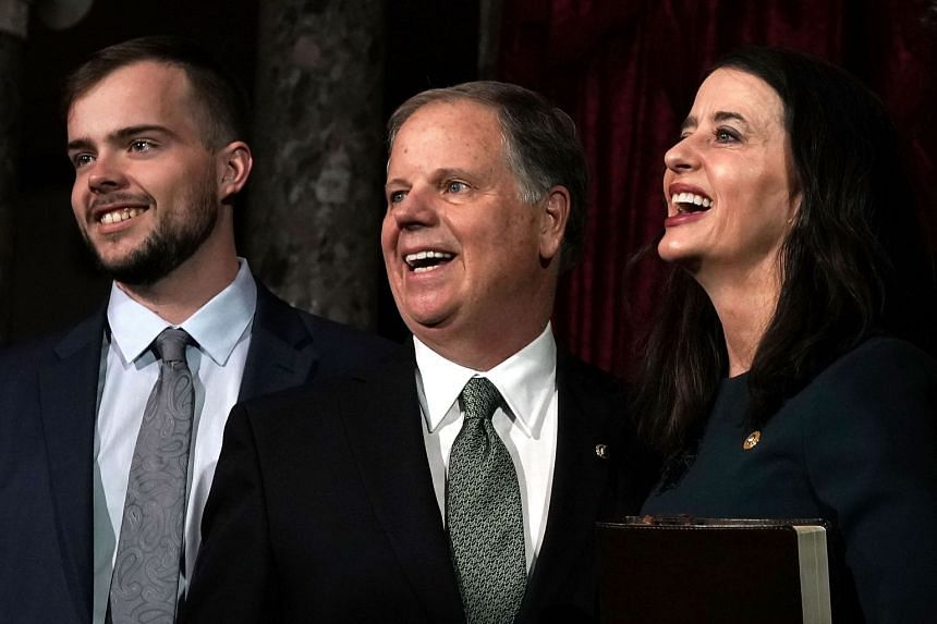Senator Doug Jones with son Carson (left) and wife Louise after the ceremony.