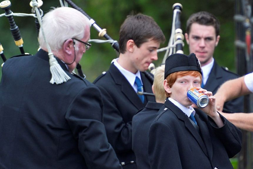 A boy drinking Irn Bru as he and other members of the Kelso pipe band prepare to play in Scotland in 2013.