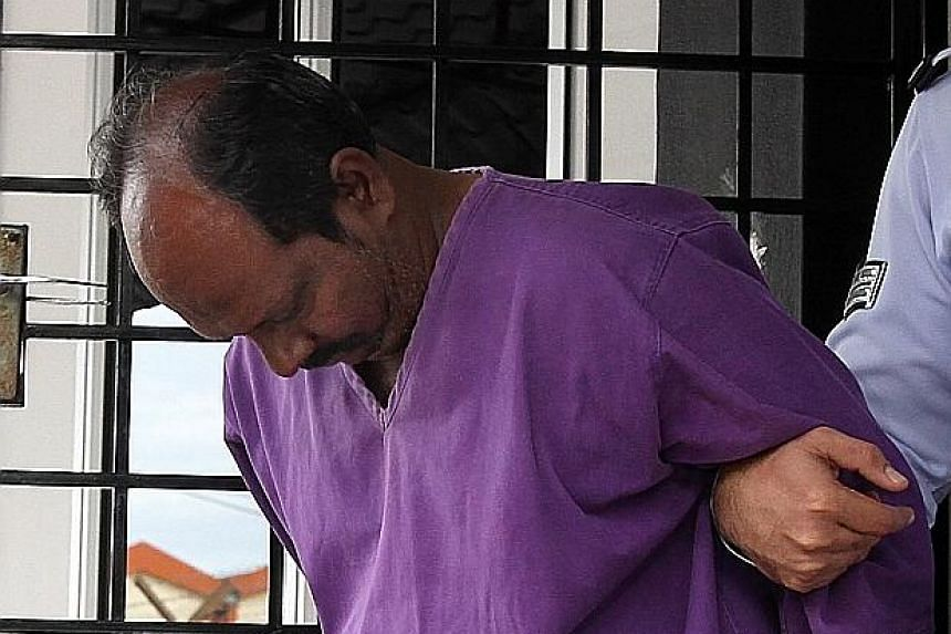 The 54-year-old suspect being led away after police obtained a four-day remand order yesterday.