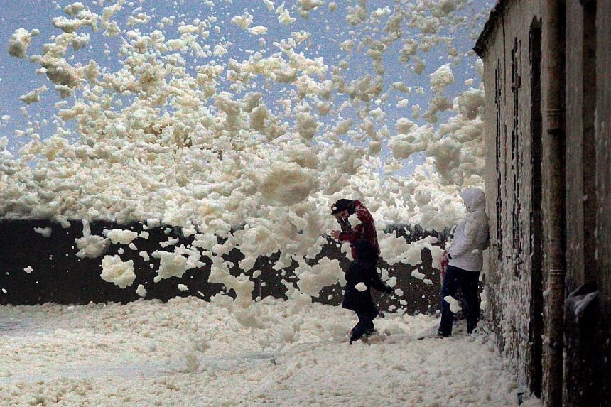 People surrounded by floating sea foam on the Brittany coast after Storm Eleanor hit Saint-Guenole in western France on Wednesday. Eleanor, the fourth winter storm to hit Europe since last month, swept into the continent on Wednesday after battering