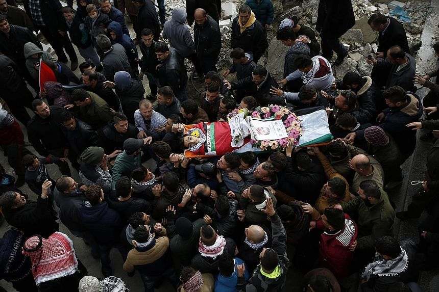 Mourners in the village of Deir Nizam, north of Ramallah in the occupied West Bank, at the funeral of 17-year-old Palestinian Musab Firas al-Tamimi yesterday. The teenager was killed during clashes with the Israeli army a day earlier.