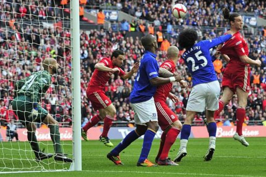 Liverpool's then striker Andy Carroll (right) scores their second goal of the FA Cup semi-final football match between Everton and Liverpool at Wembley Stadium in London, on April 14, 2012.
