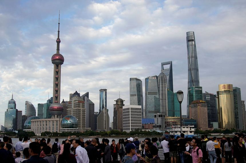 People visit the Bund in front of Shanghai's financial district of Pudong on Sept 28, 2017.