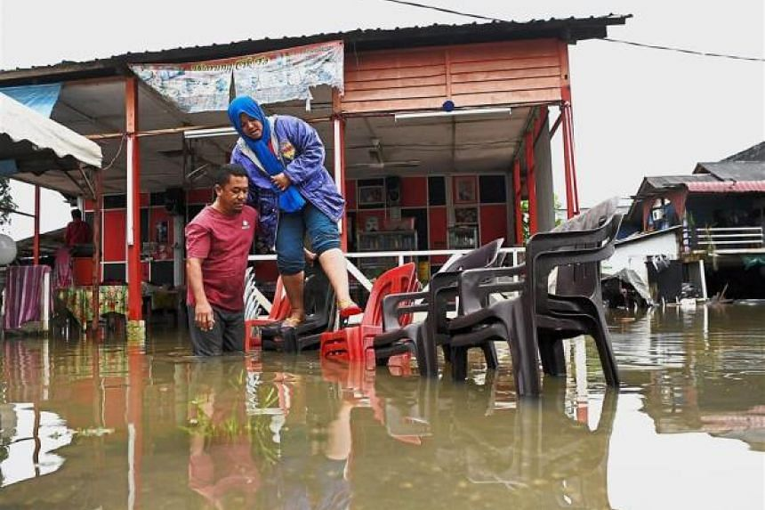 Johor residents Rasau Mohamad Sukri, 45, helping his wife Ita Daud, 41, to cross a flooded pathway on plastic chairs.