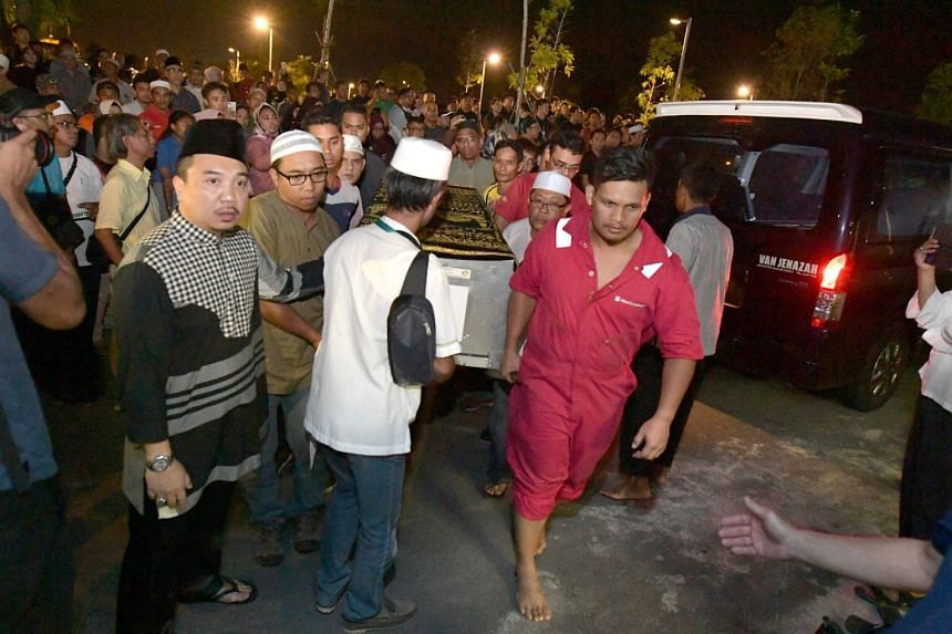 The casket of Nur Amalina Rosli, 21, arrives at the Muslim cemetery in Choa Chu Kang on Thursday night.