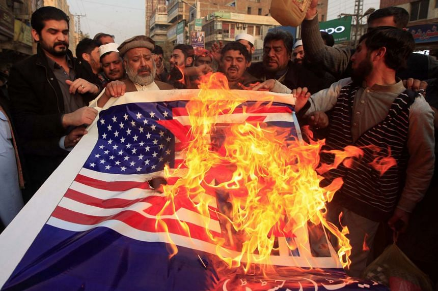 Pakistani traders shout slogans and burn a US flag with a picture of Donald Trump in Peshawar, Jan 5, 2018.