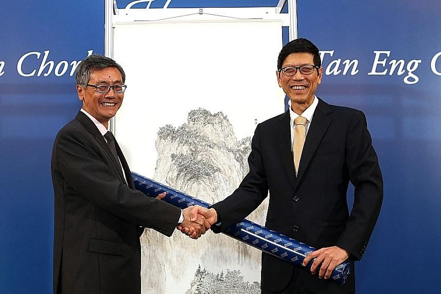 Professor Tan Chorh Chuan (right) presenting a painting he did to NUS president Tan Eng Chye, his successor. In the background is another painting by Prof Tan Chorh Chuan.