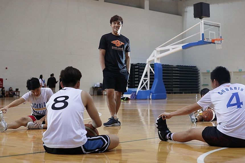 National basketballer Wong Wei Long (centre) will be conducting lessons at the Sports Hub Basketball Academy, a training programme that was launched at the OCBC Arena yesterday in a tie-up with his academy.
