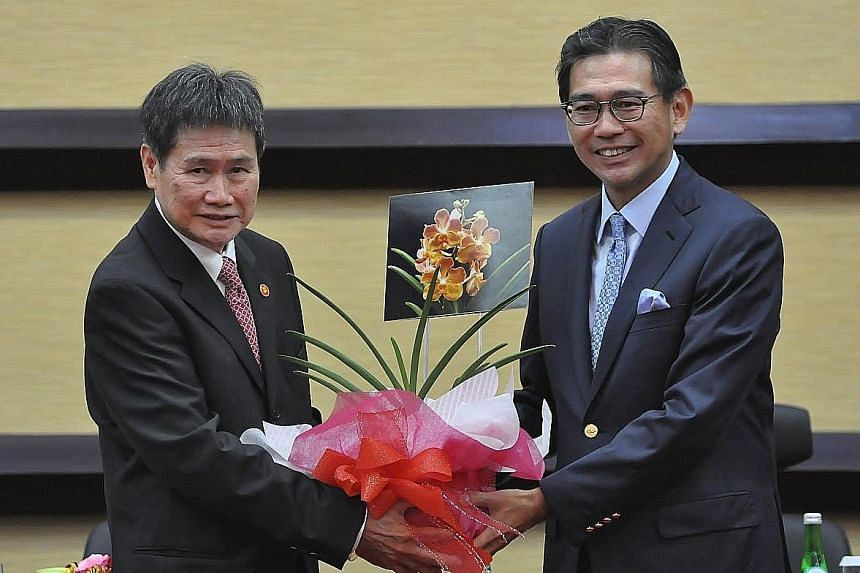 Singapore Ambassador Tan Hung Seng (right) presenting the new Secretary-General of Asean, Mr Lim Jock Hoi, with a special hybrid orchid at a ceremony in Jakarta yesterday.