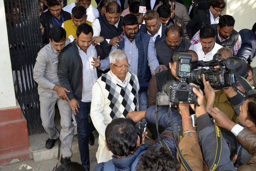 Former chief minister of Bihar state Lalu Prasad Yadav (centre) walks as he has being taken to police custody after found guilty at a special CBI Court in Ranchi on Dec 23, 2017.