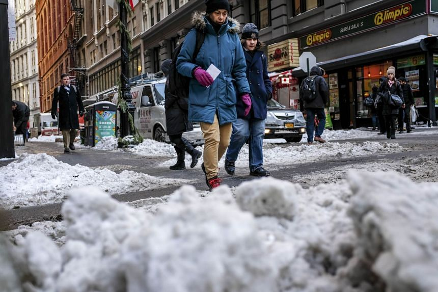 Pedestrians walk through a slushy intersection in the Financial District, Jan 5, 2018 in New York City.